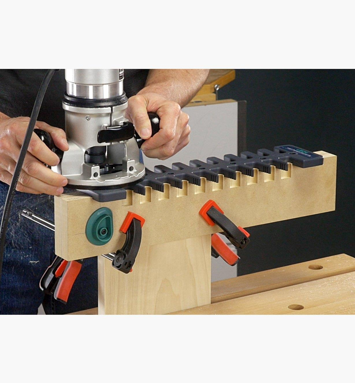 A man using a handheld router with the Leigh Through Dovetail Jig to cut dovetails