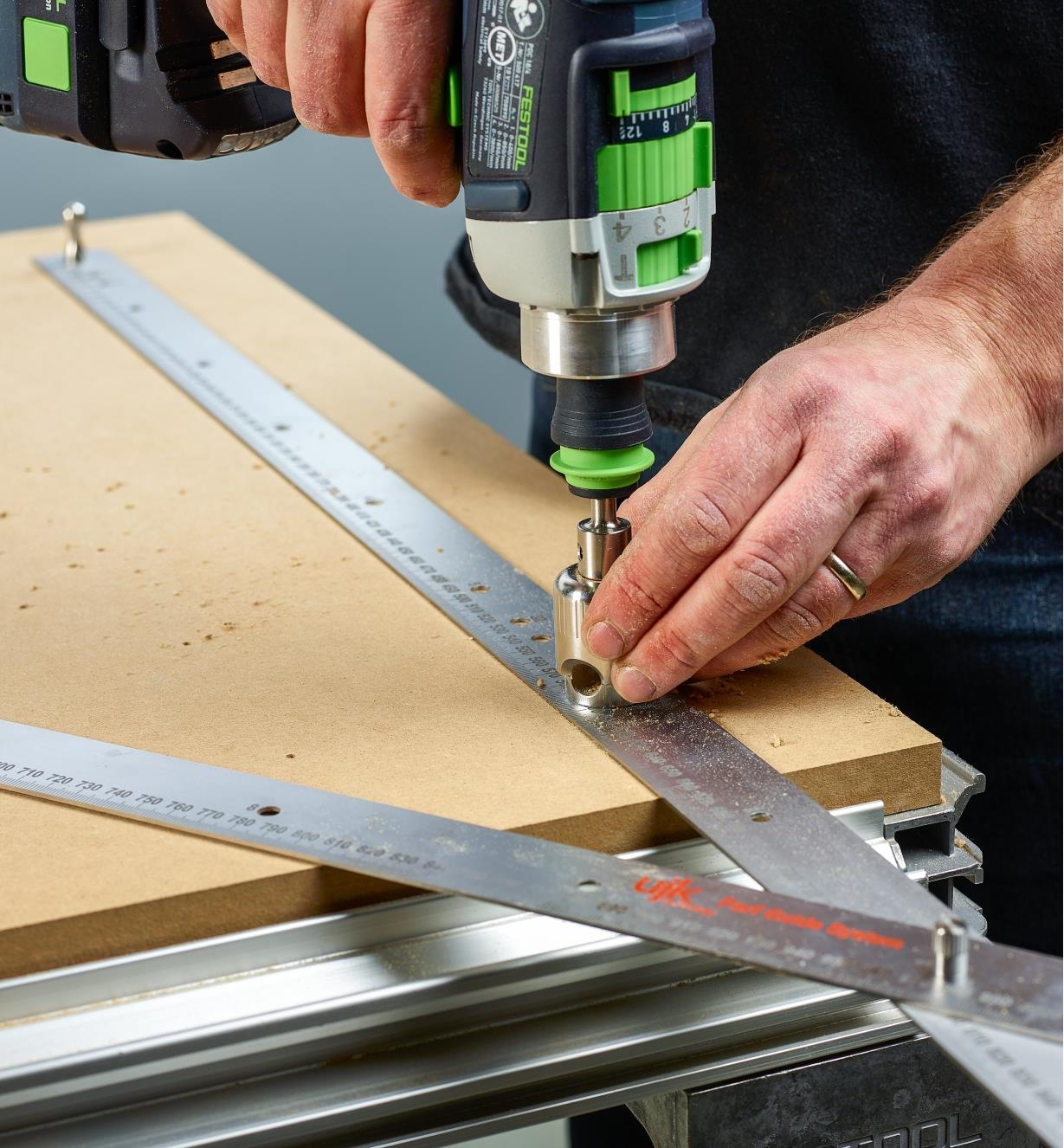 Using the pair of 1m rules as templates for drilling starter holes in a work surface