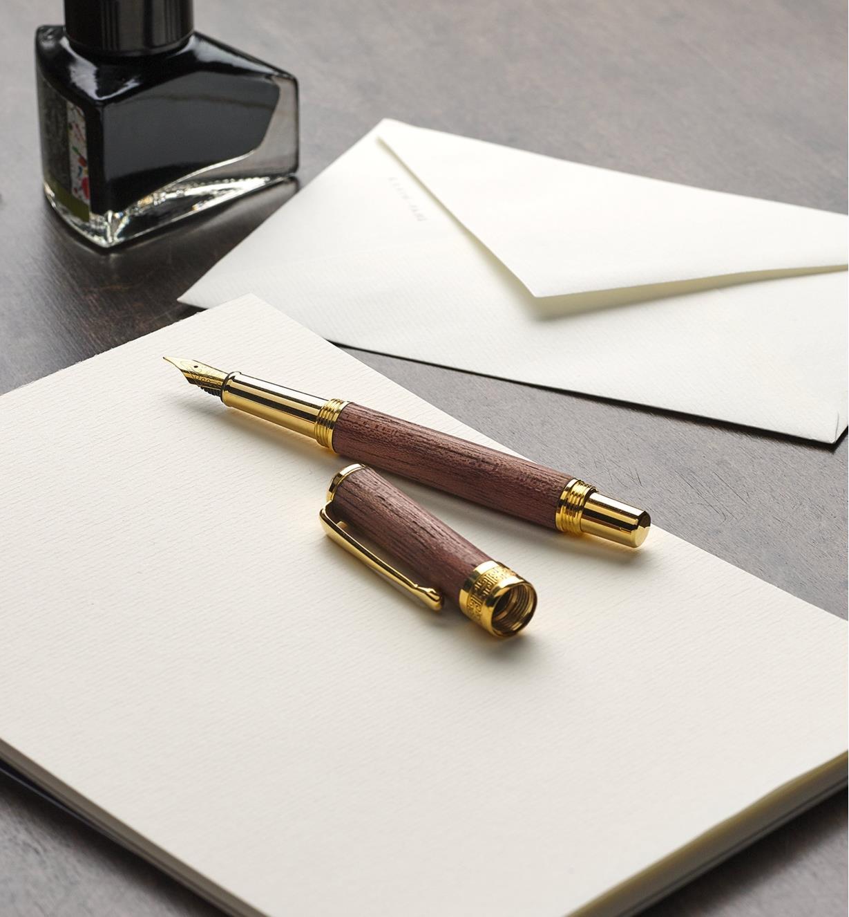 Stylo à bille roulante New Series doré reposant sur un bloc-notes avec son capuchon