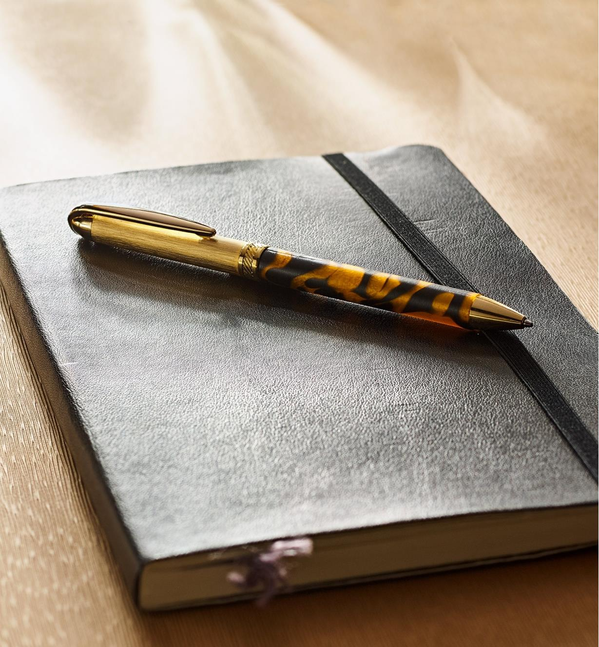 Example of a Surfix Duo gold/gunmetal pen turned from an acrylic acetate blank, lying on a closed notebook