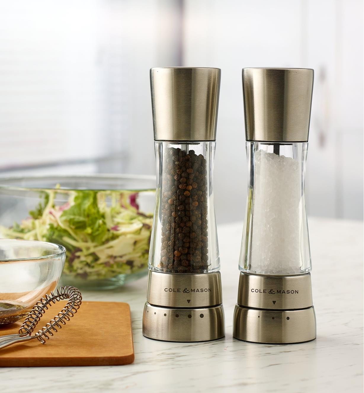 A set of Cole & Mason salt and pepper mills standing on a marble countertop next to a bowl of salad
