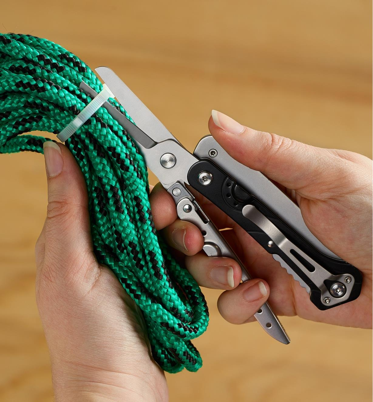 Ciseaux de l'outil multifonction servant à couper une attache autobloquante qui maintient une corde enroulée