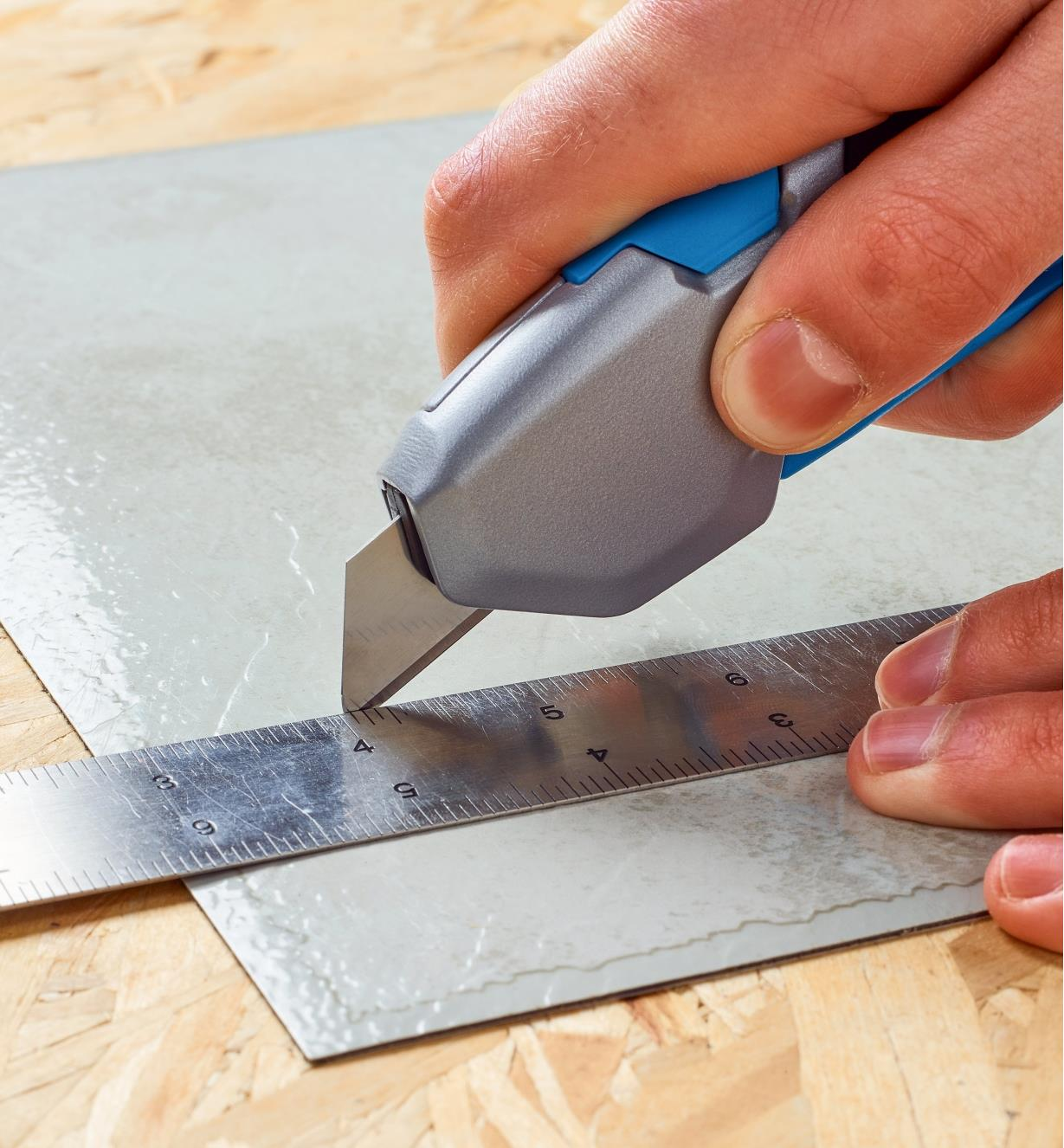 Safety utility knife cutting linoleum along the edge of a steel ruler