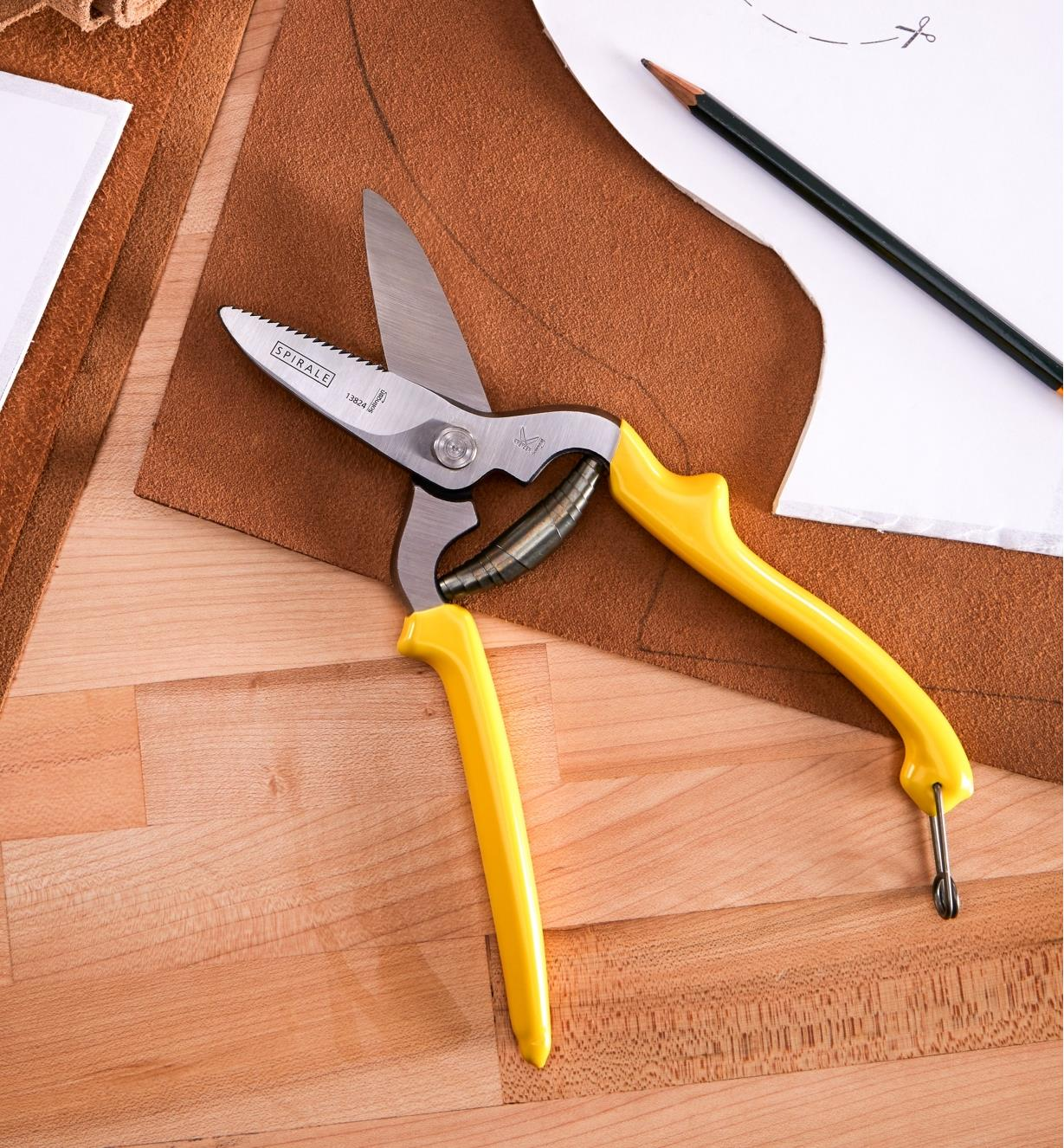 Leather shears lying on a table with a paper pattern and a piece of leather marked for cutting
