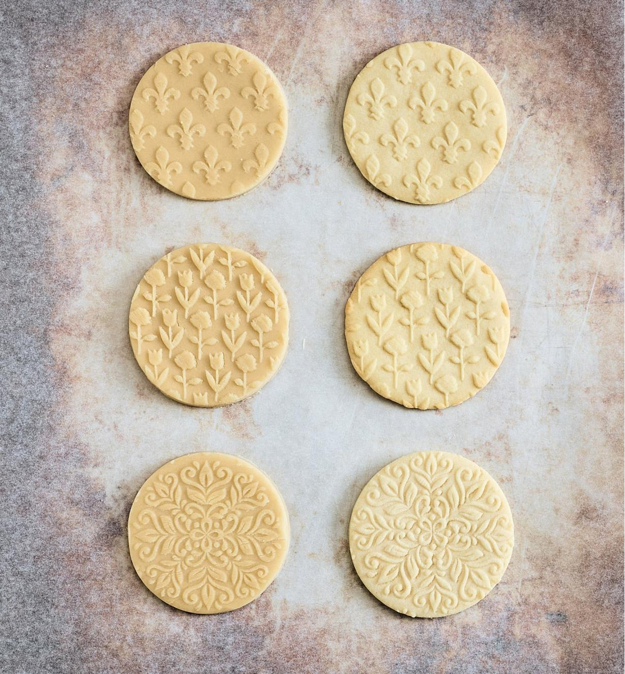 Cookies embossed by embossing rolling pins in pairs of each pattern, Fleur de Lis, Roses and Tulips and Kaleidoscope, comparing before and after baking