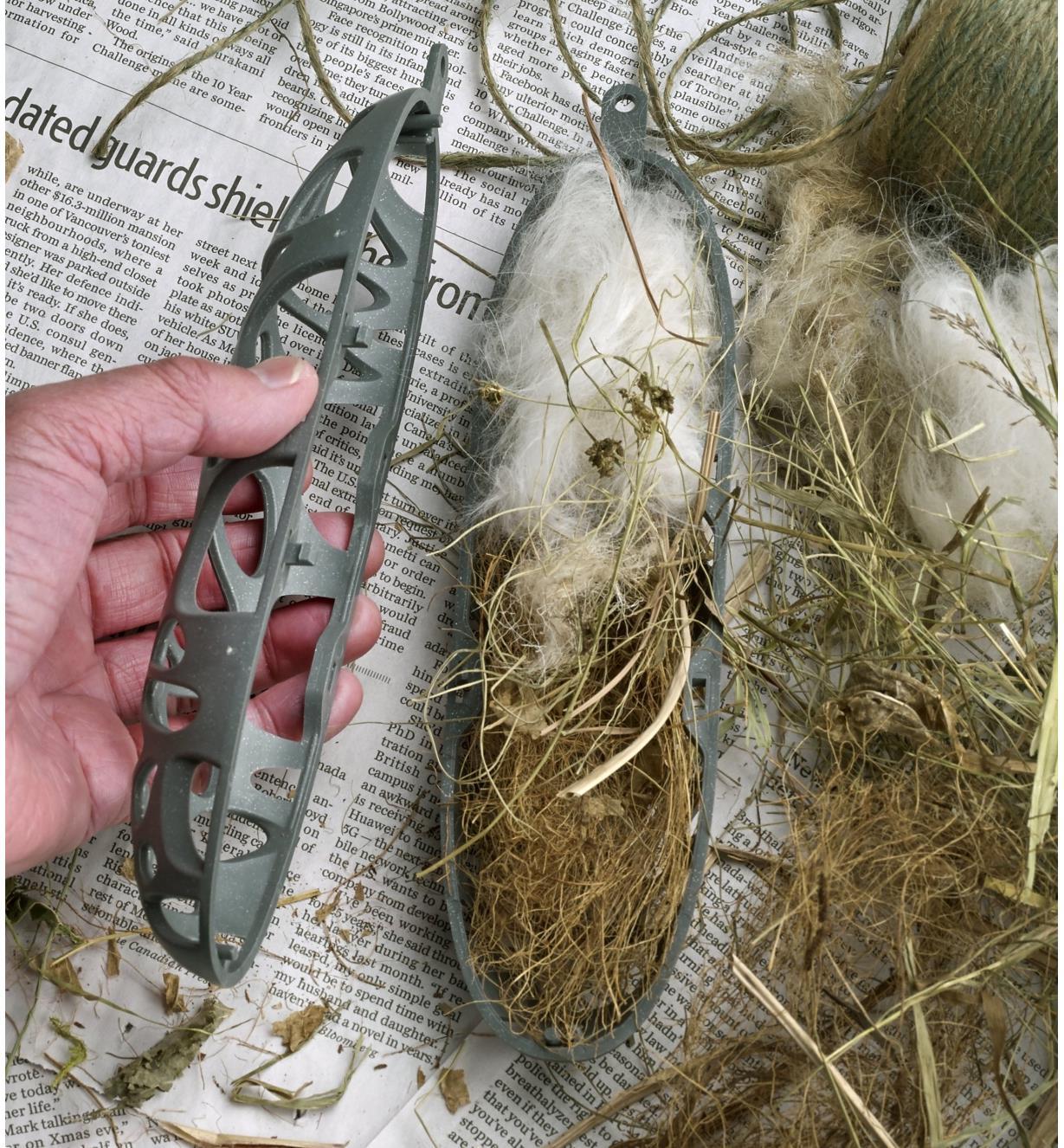 Mangeoire à suif pour oiseaux contenant des poils d'animaux, de la ficelle et de la paille pour aider les oiseaux à construire leur nid