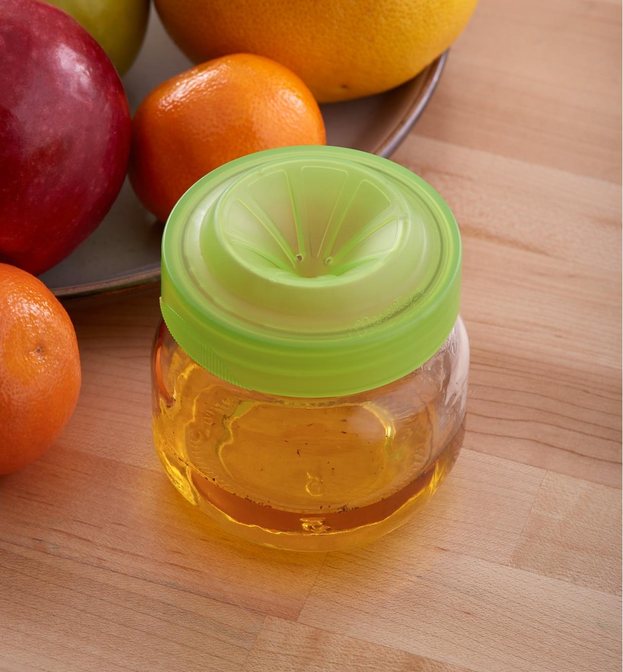 Fruit Fly Trap Cap threaded onto a small jar with liquid inside