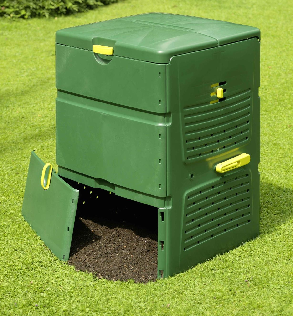 Composter in a garden with the bottom compartment open, releasing finished compost