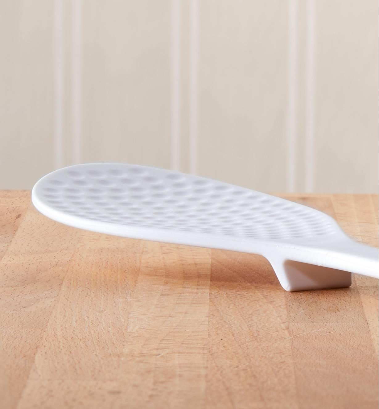 Rice paddle on a wooden counter, with a small foot on the underside raising the end off the countertop