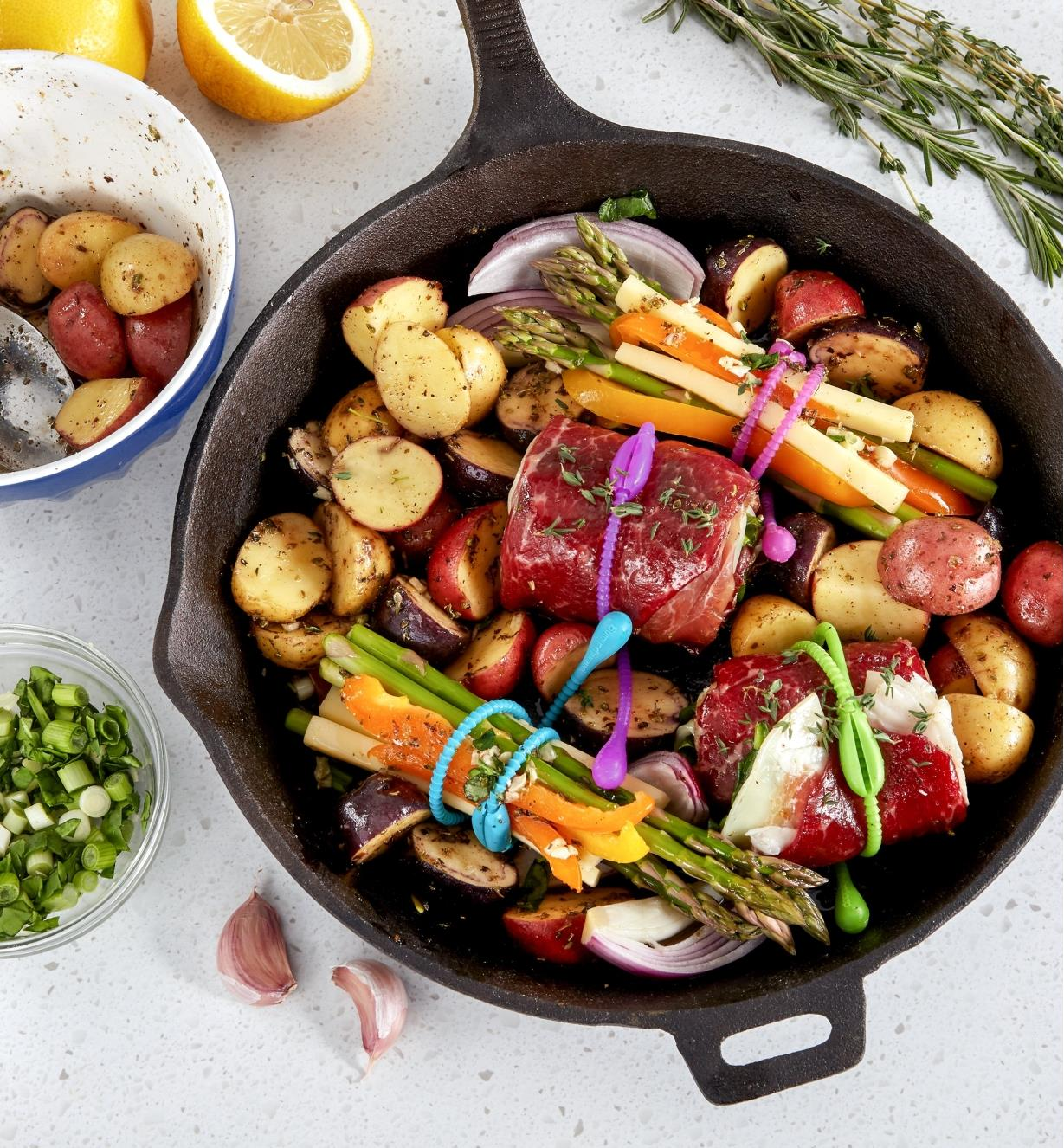 Vegetables and beef roulades secured with FoodLoop in a cast-iron pan before cooking