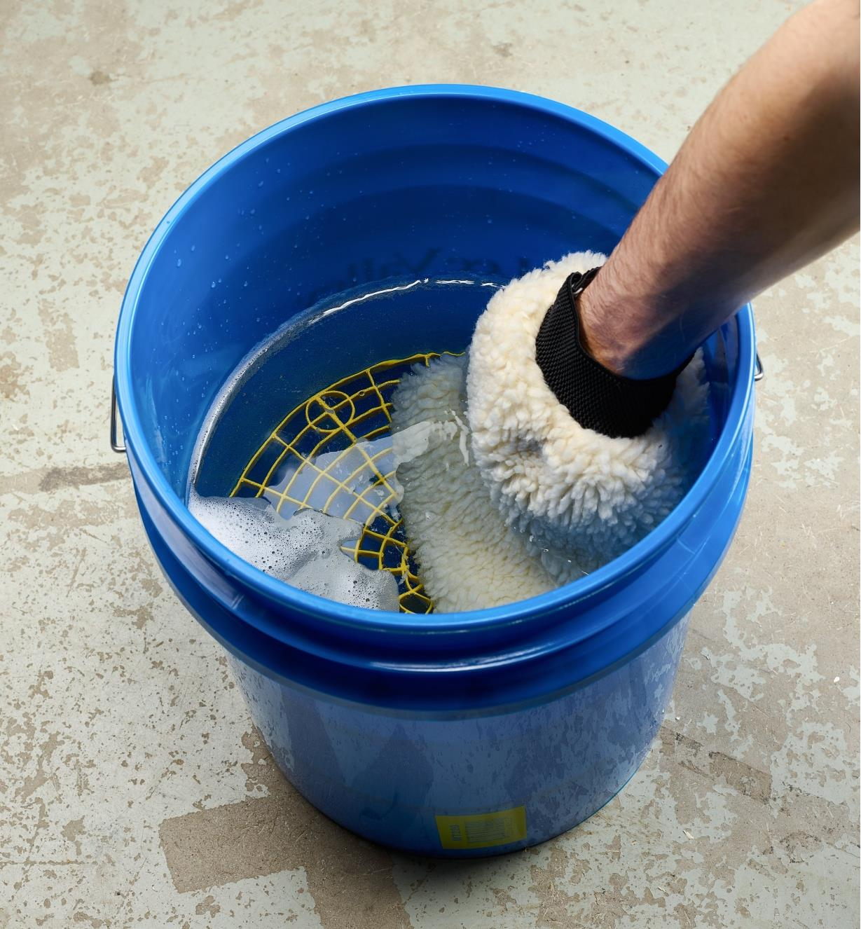 In a water-filled pail, a wash mitt is rubbed against the wash pail insert to loosen trapped grit