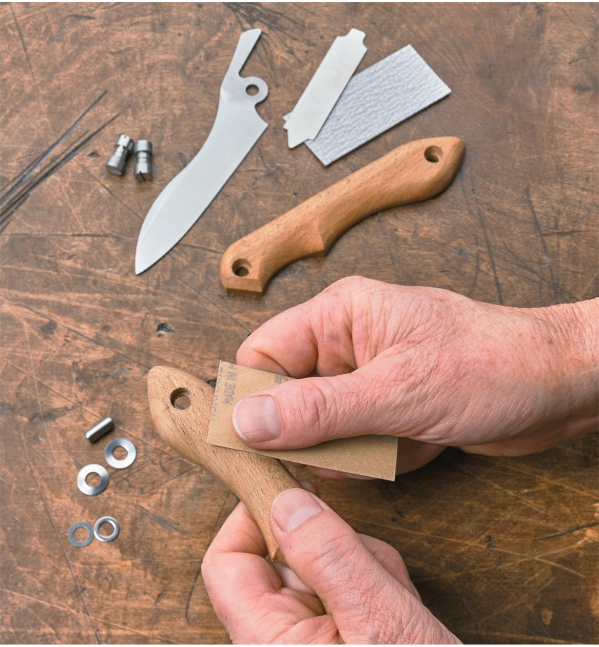 Sanding the knife handle after carving