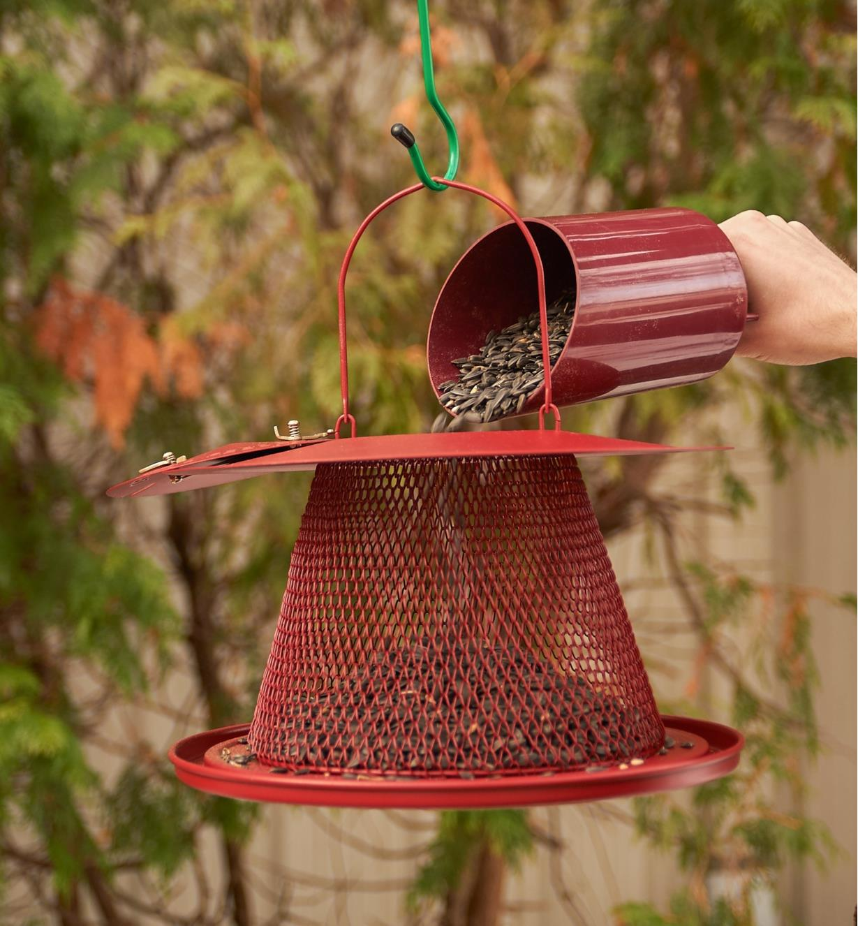 Seeds poured into collapsible bird feeder through an opening in the top