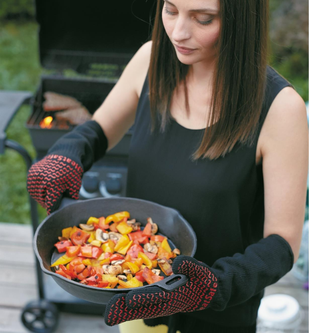 Woman wearing barbecue gloves holding cast-iron pan that she has removed from barbecue