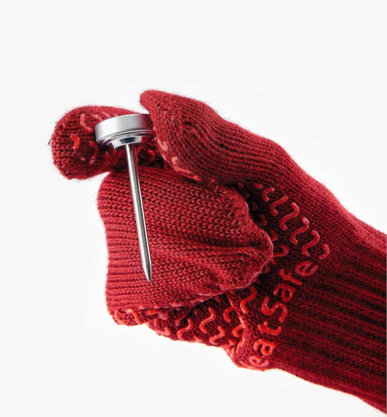 Personne portant des gants de cuisine pour tenir un thermomètre de cuisson