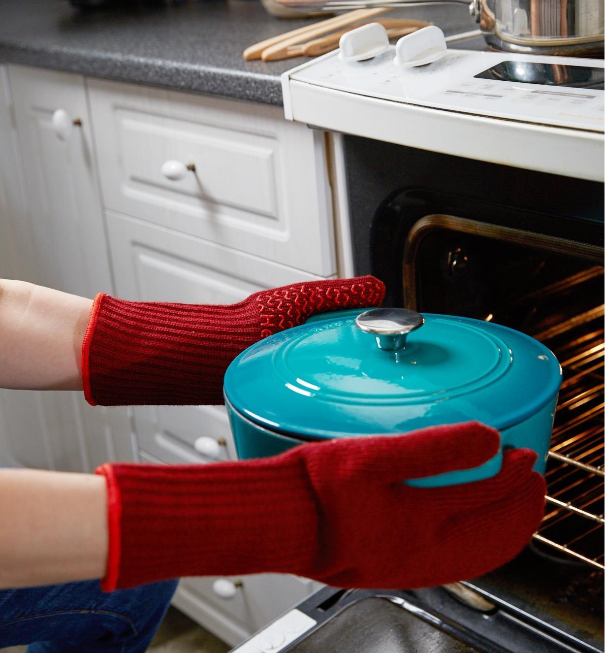 Personne portant des gants de cuisine pour retirer une cocotte en fonte du four