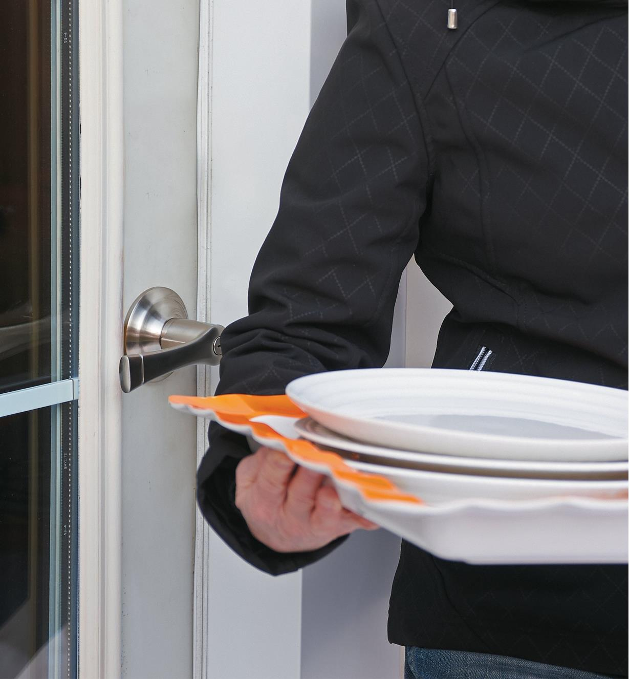 A woman carrying a tray of dishes opens a door with the push of her elbow on the handle