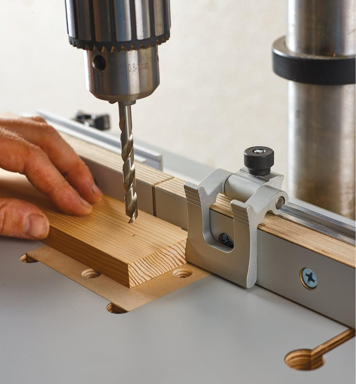 "A Veritas 1 1/2"" flip stop mounted in the T-track on the drill-press table's fence"