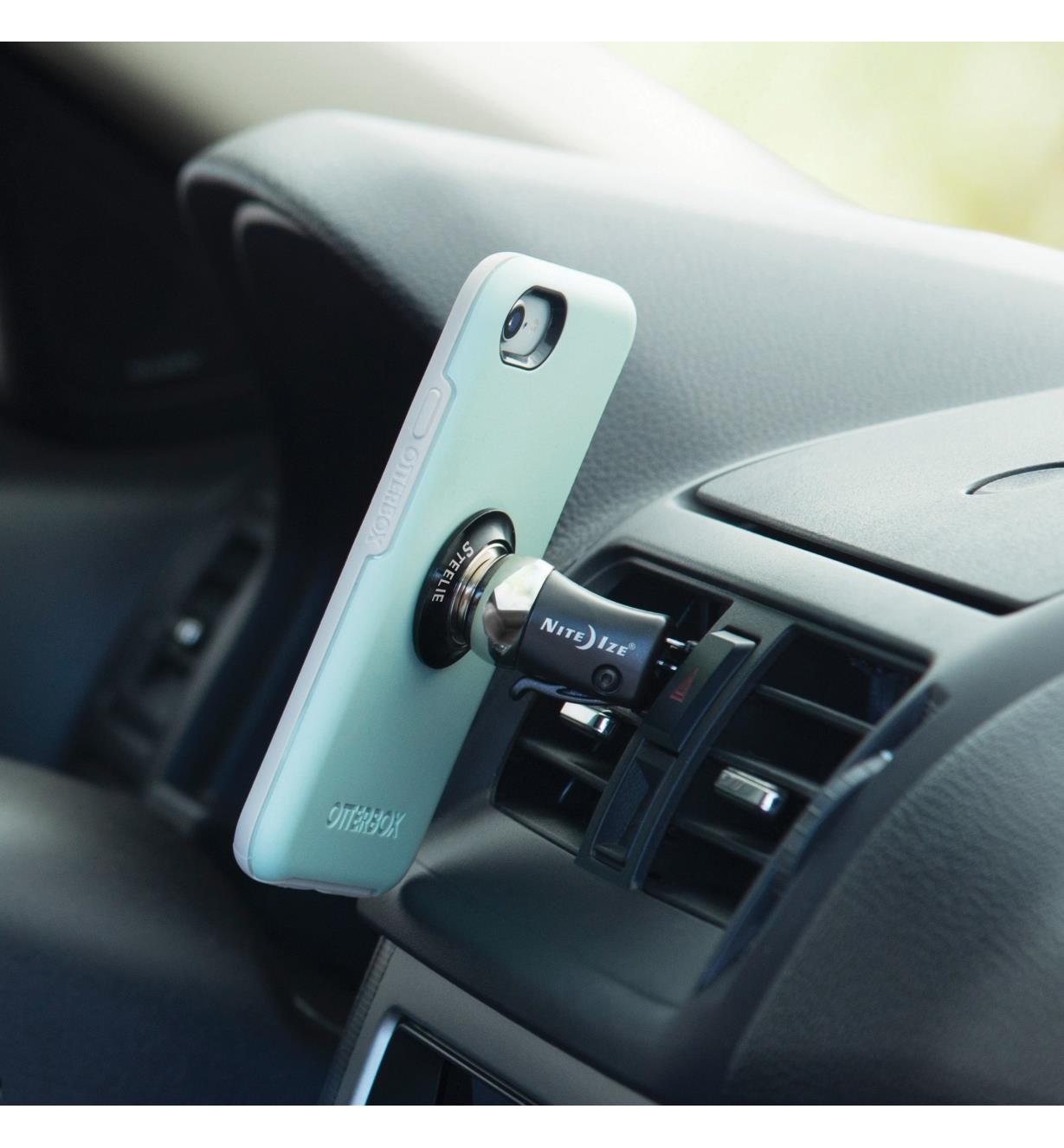 Cell phone attached to the vent-mount kit installed in a car vent