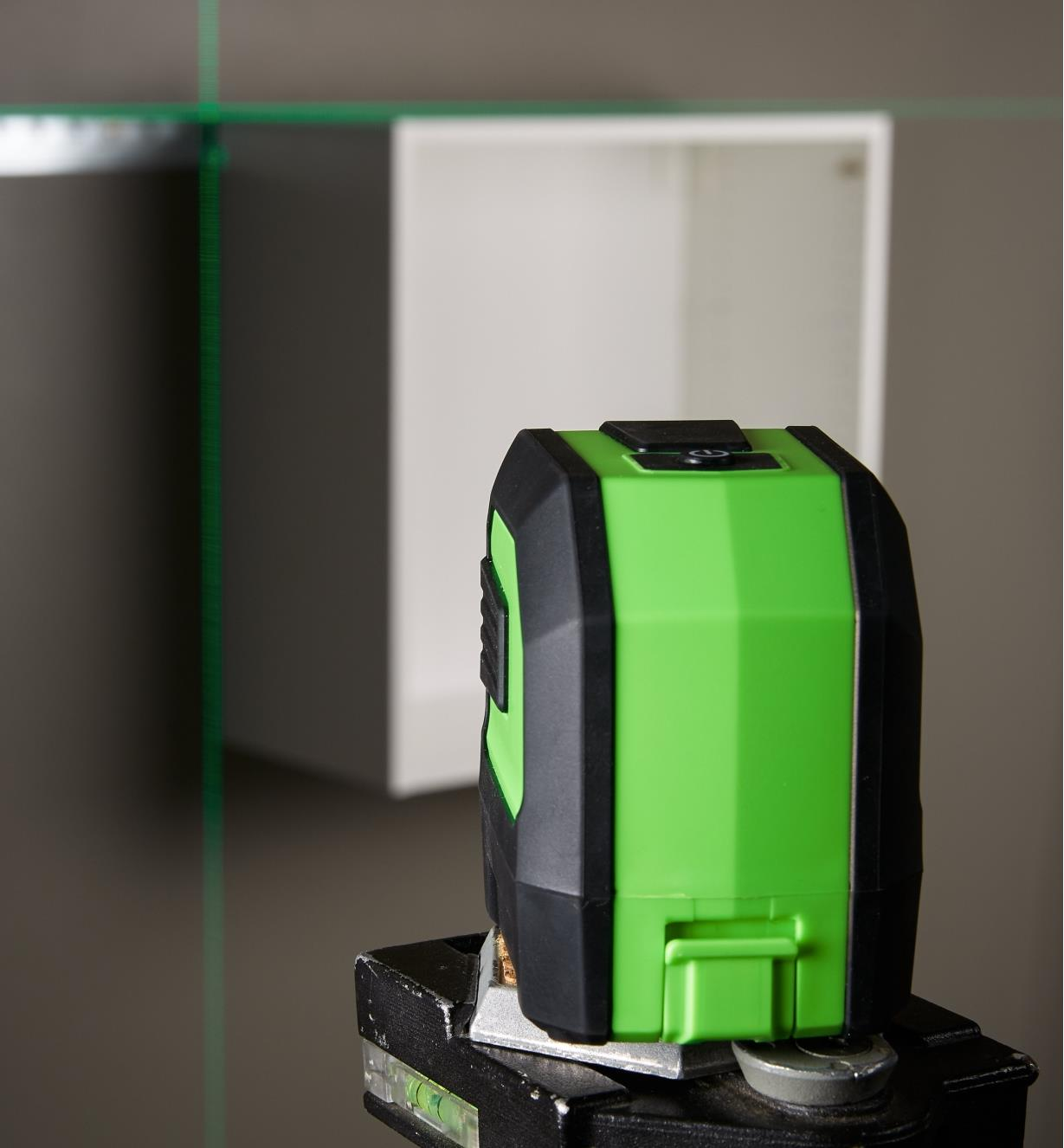 Back view of the green crosshair laser level with its projected beam showing that an installed wall cabinet is level and plumb