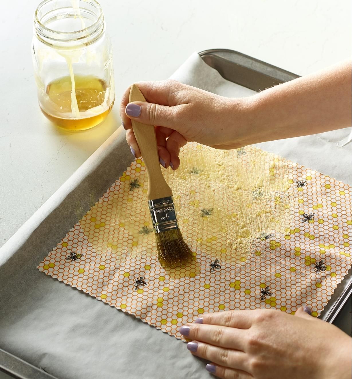 Brushing wax on to a cloth to create a beeswax wrap