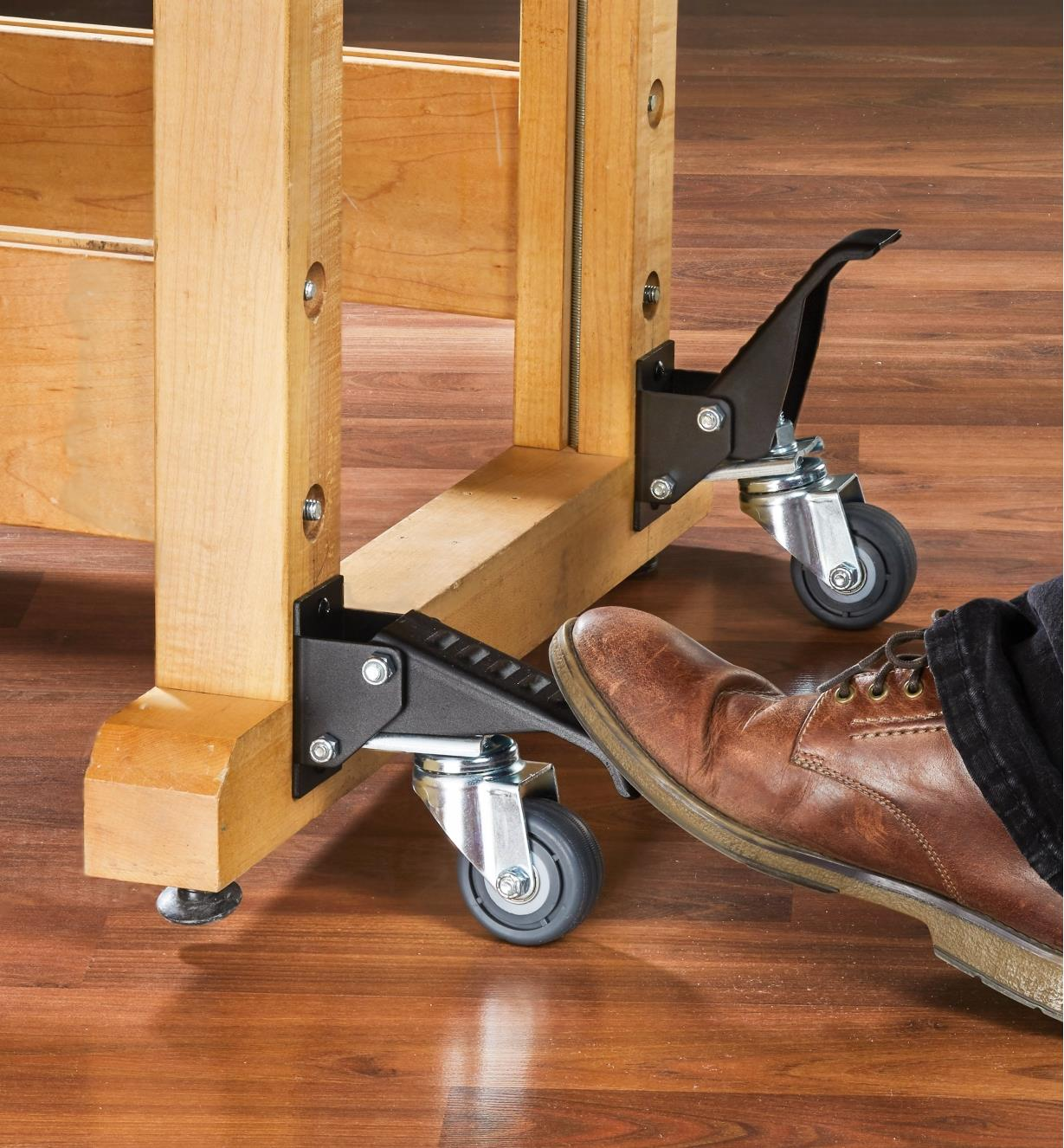 A foot depresses the pedal of a workbench caster, lowering it into position to contact the floor