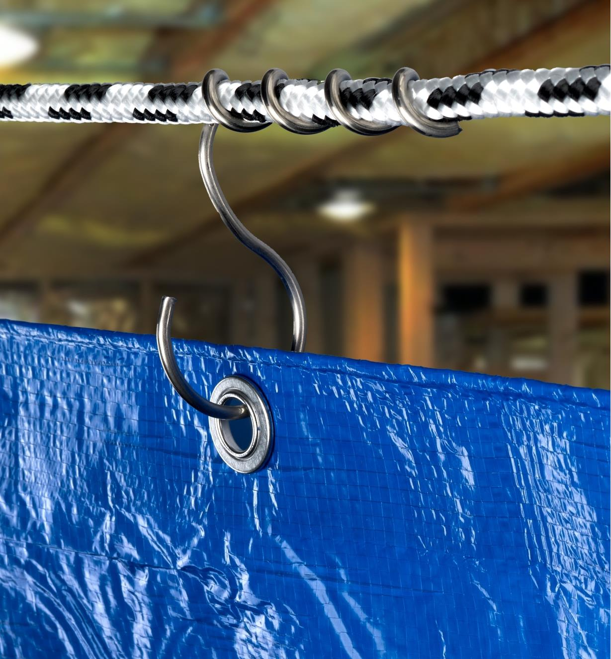 A tarp hanging from a line hook secured to a rope