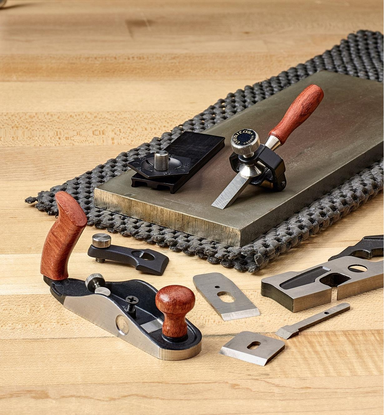 A chisel blade held in the miniature honing guide sits beside the angle jig on a sharpening stone with other small blades nearby