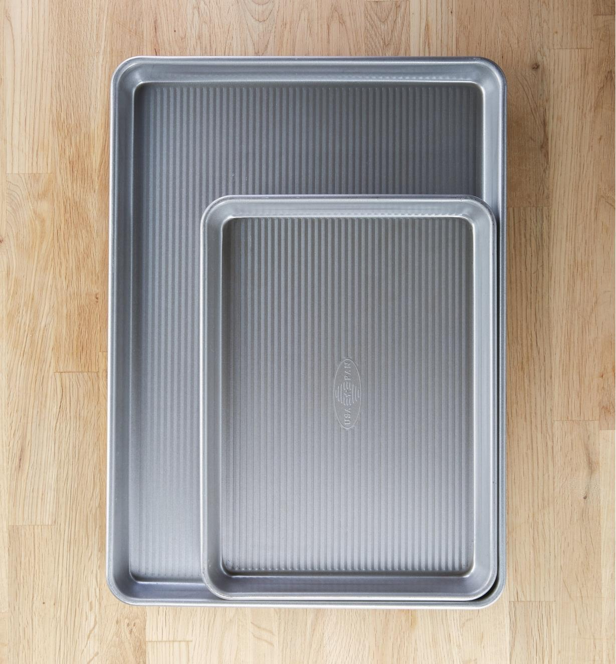 A quarter sheet baking pan nested in a half sheet baking pan to compare size