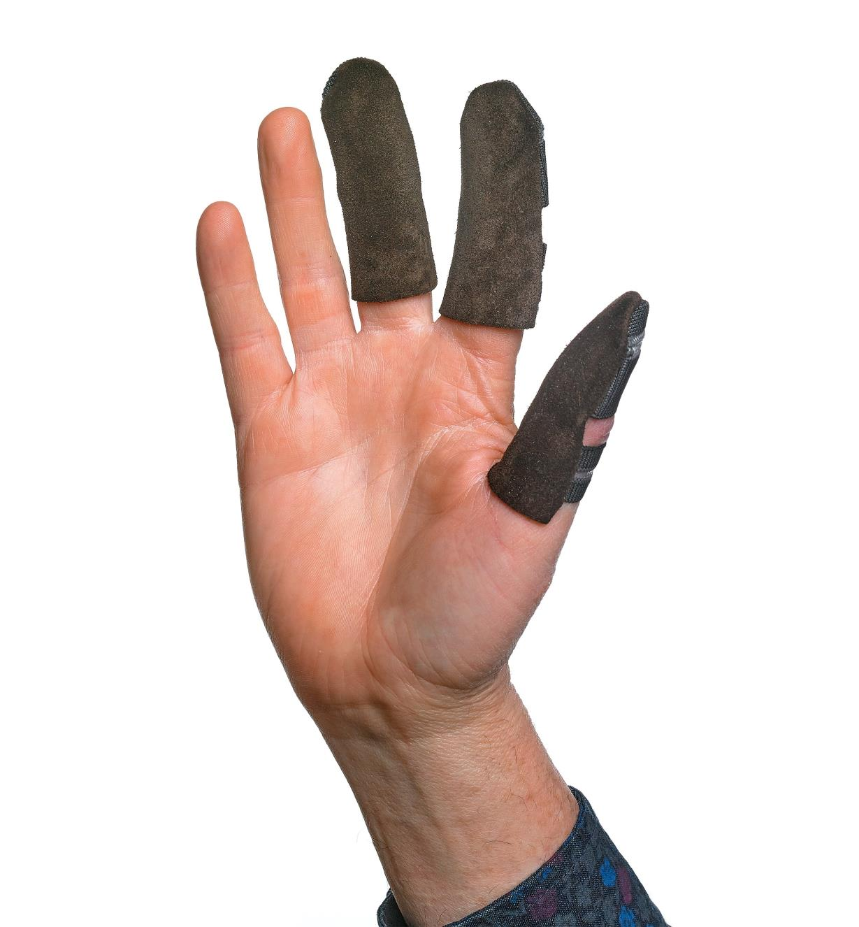 A raised hand wearing Leather Thumb & Finger Guards