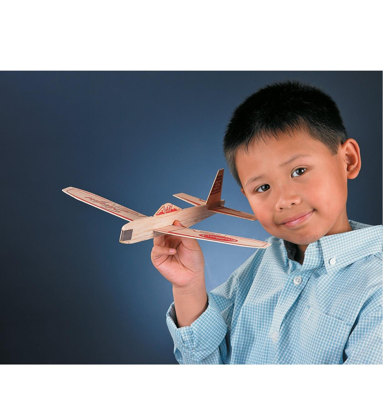 A boy plays with an assembled Balsa Glider
