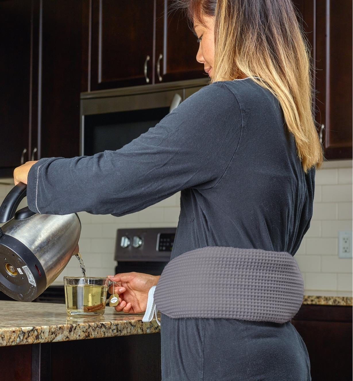 A woman wears the long hot-water bottle tied around her waist while standing in the kitchen making tea