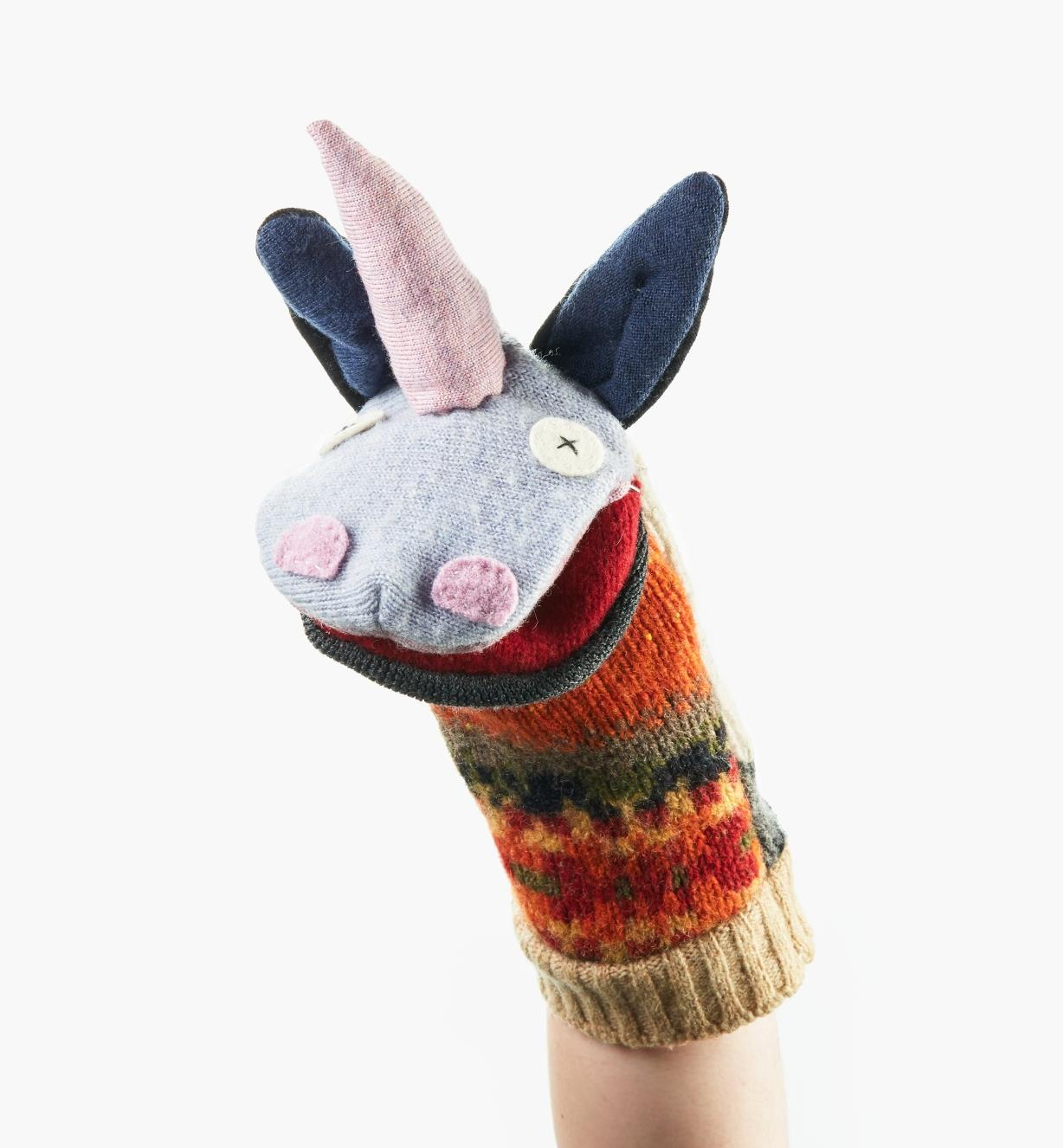 A completed unicorn puppet on a person's hand