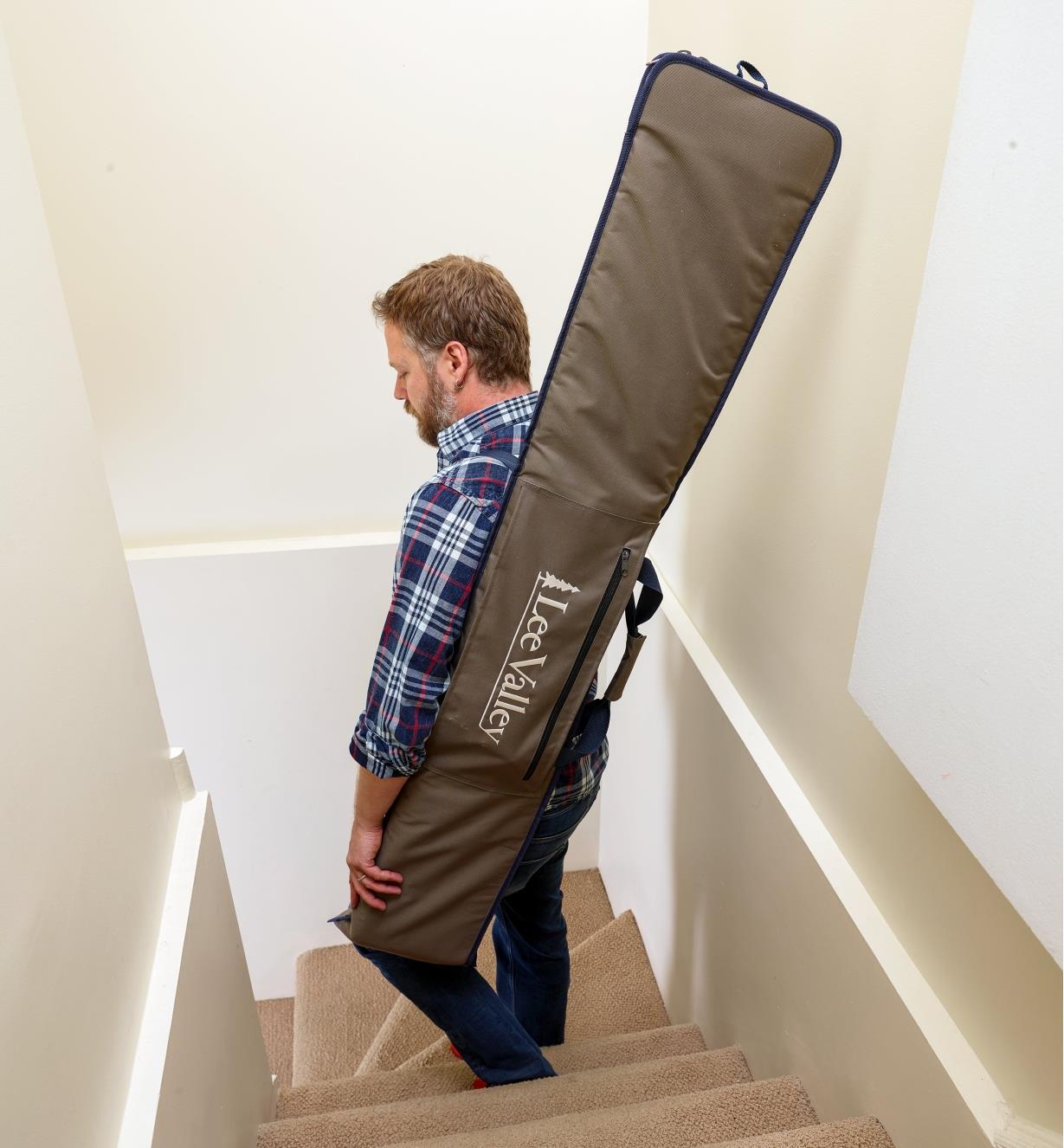 Personne transportant le petit étui pour guide de coupe en bandoulière dans un escalier