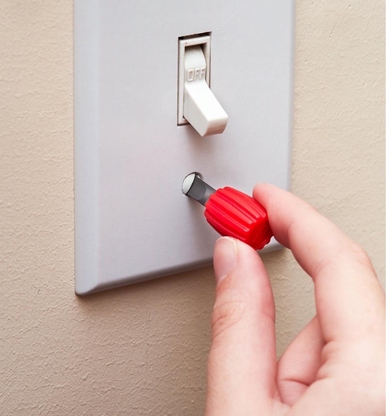 Serrage d'une vis d'une plaque d'interrupteur avec un mini porte-embout