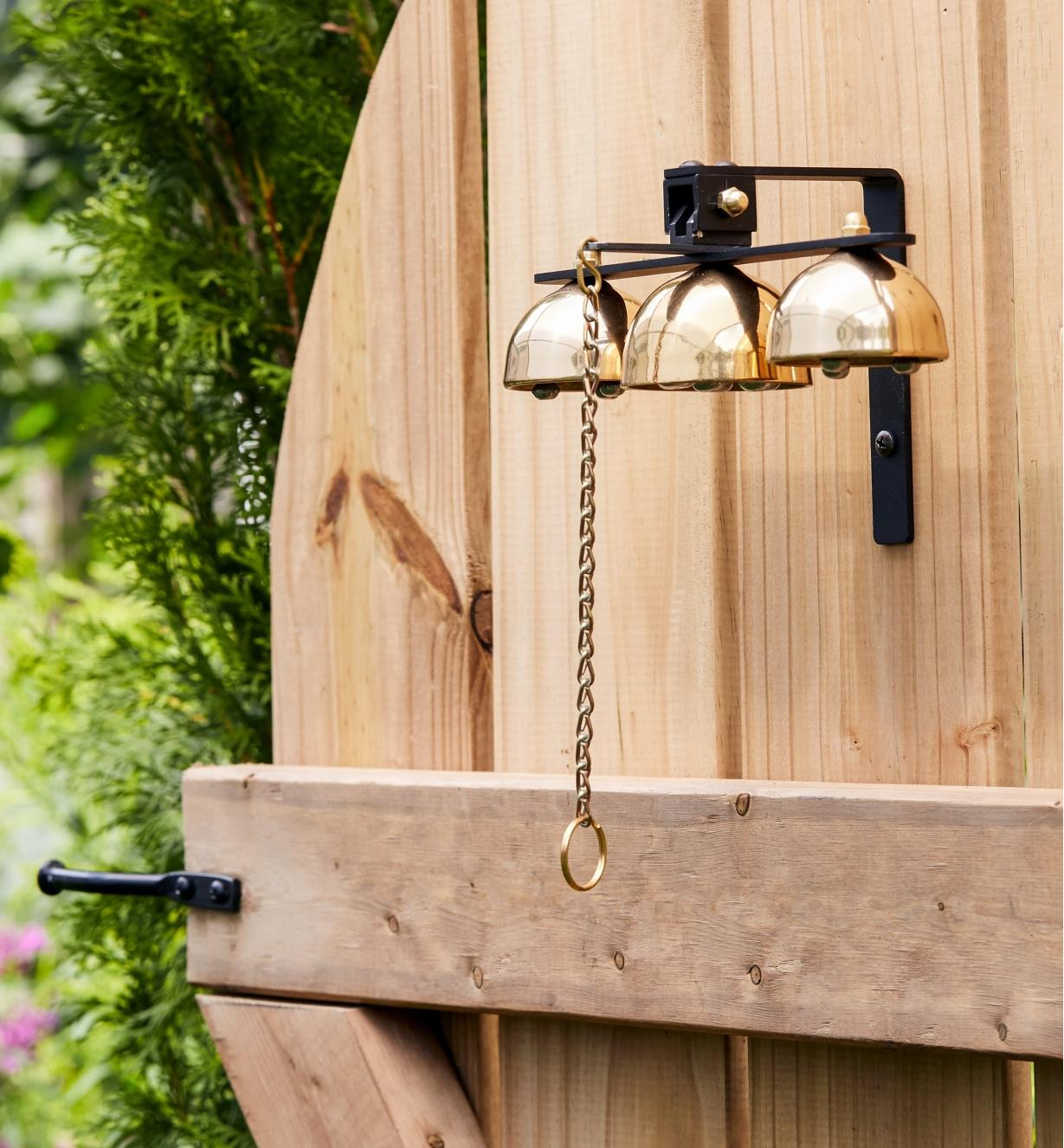 Garden bells mounted on a wooden gate
