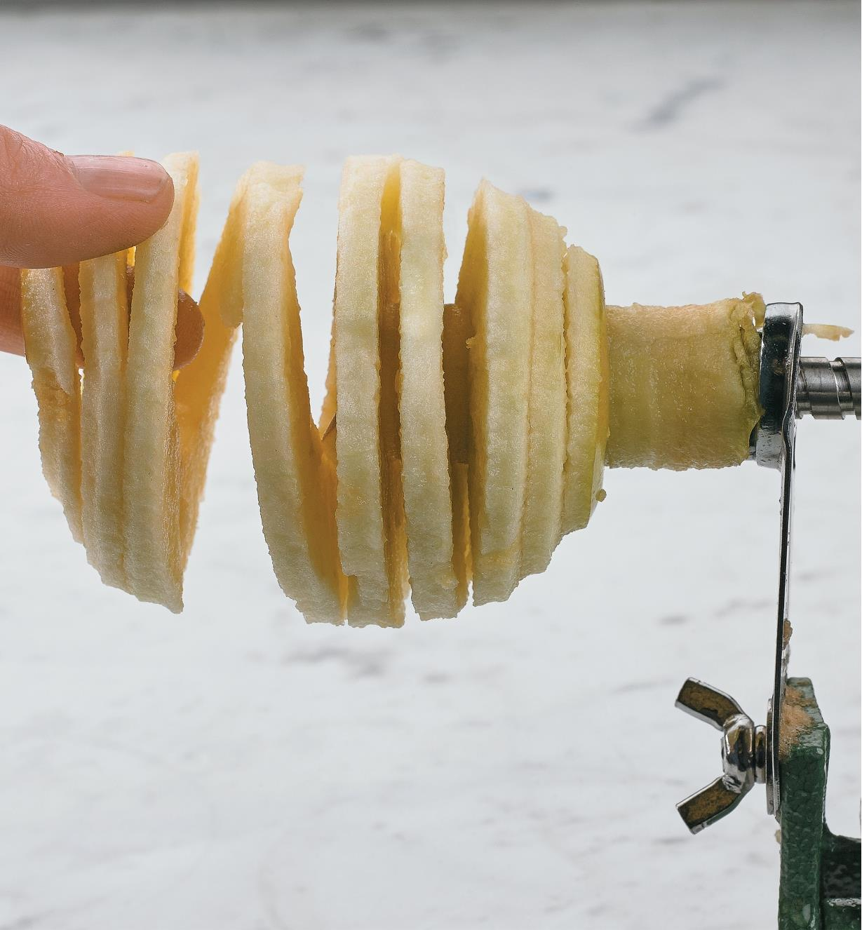 Removing a peeled, sliced and cored apple from the apple peeler