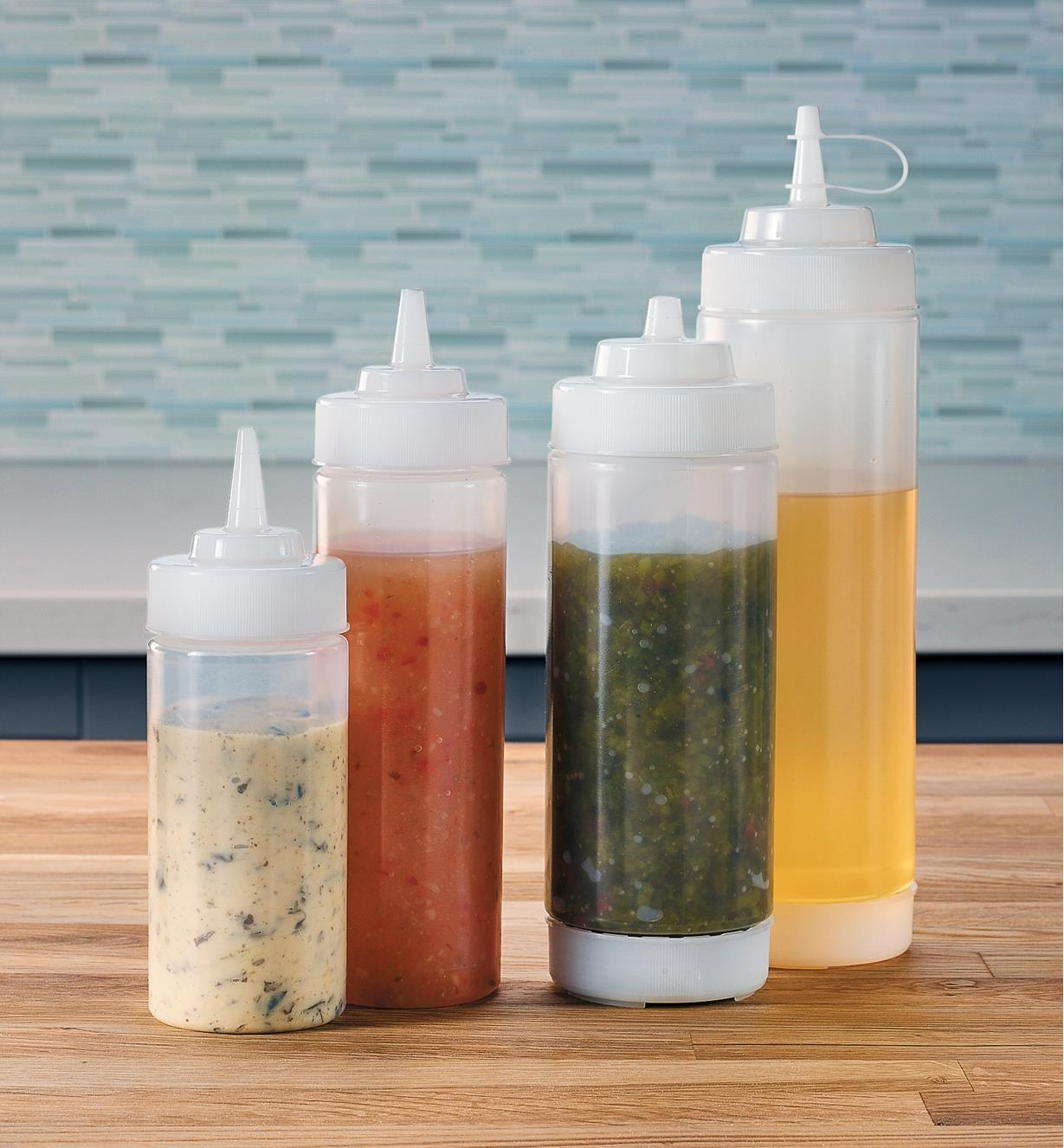 Four squeeze bottles filled with condiments