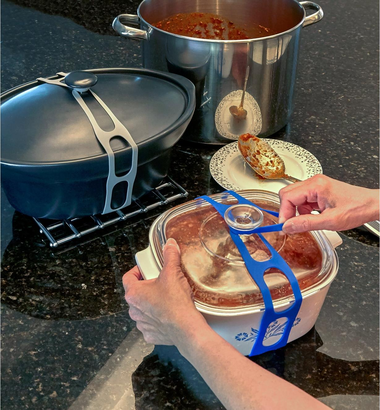 Applying the lid latch to a casserole dish, with another pot held closed using a lid latch in the background