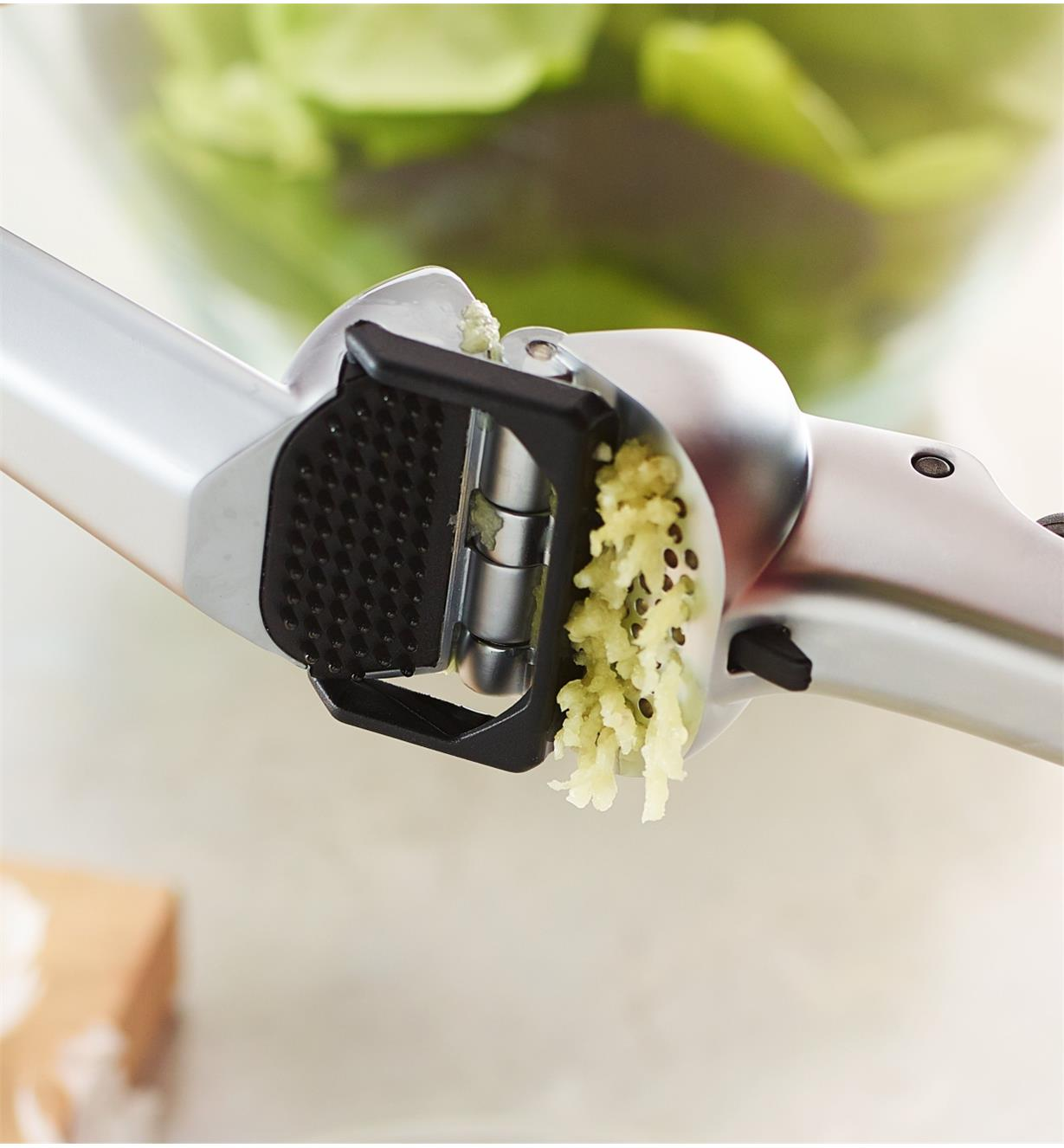 A plastic bar sweeping across the grate of the Garject Garlic Press