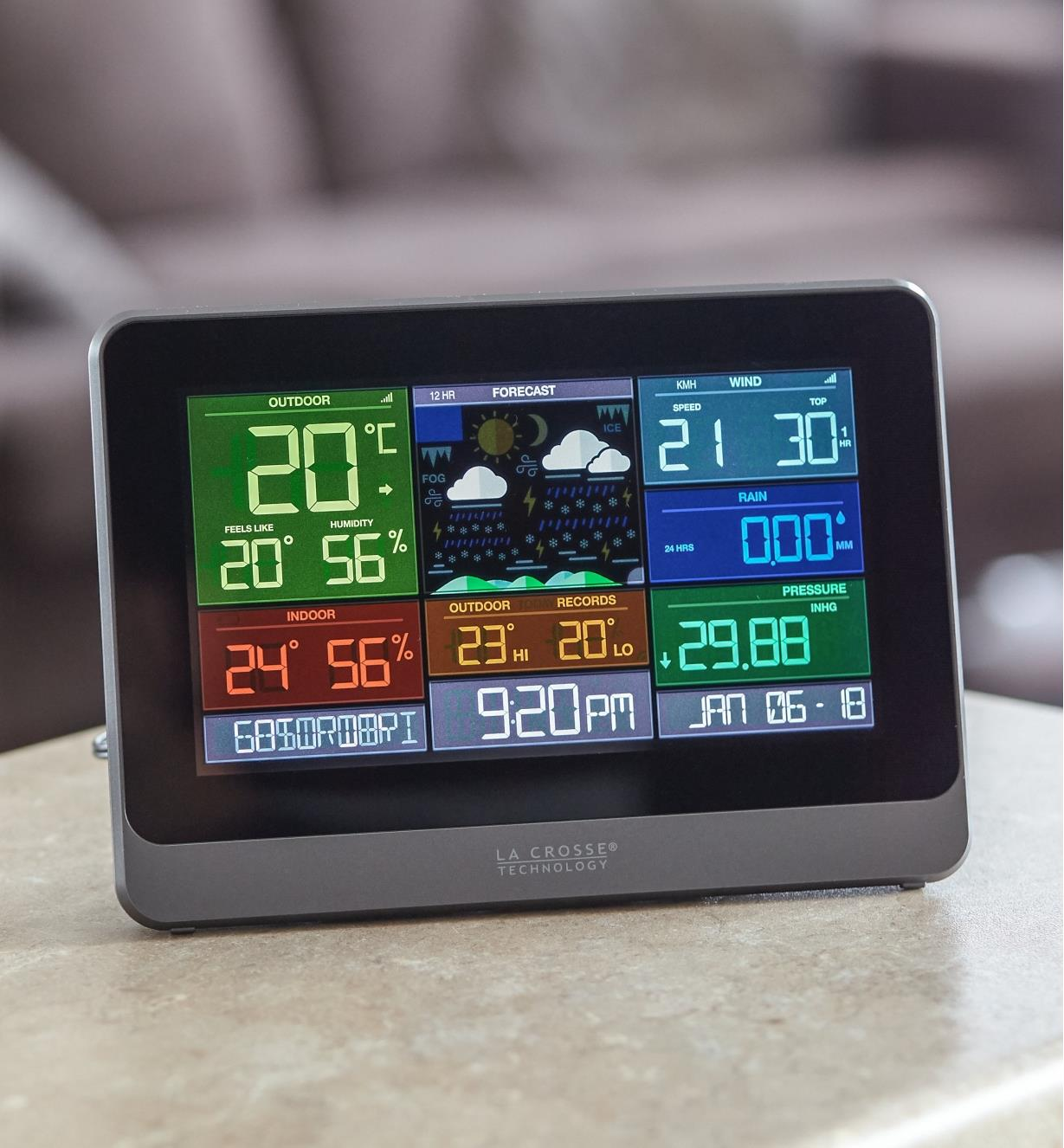 The display unit of the Wi-Fi weather station with wind and rain sits on a tabletop