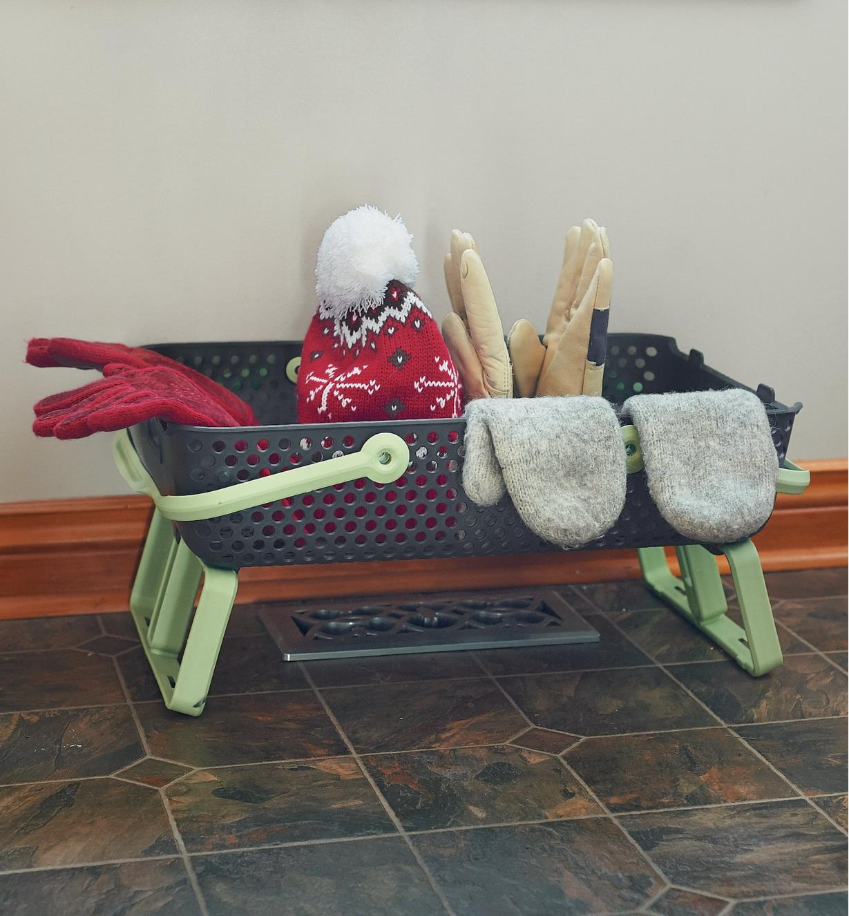 Medium Stacking Basket straddling a heat register, holding mittens and a hat