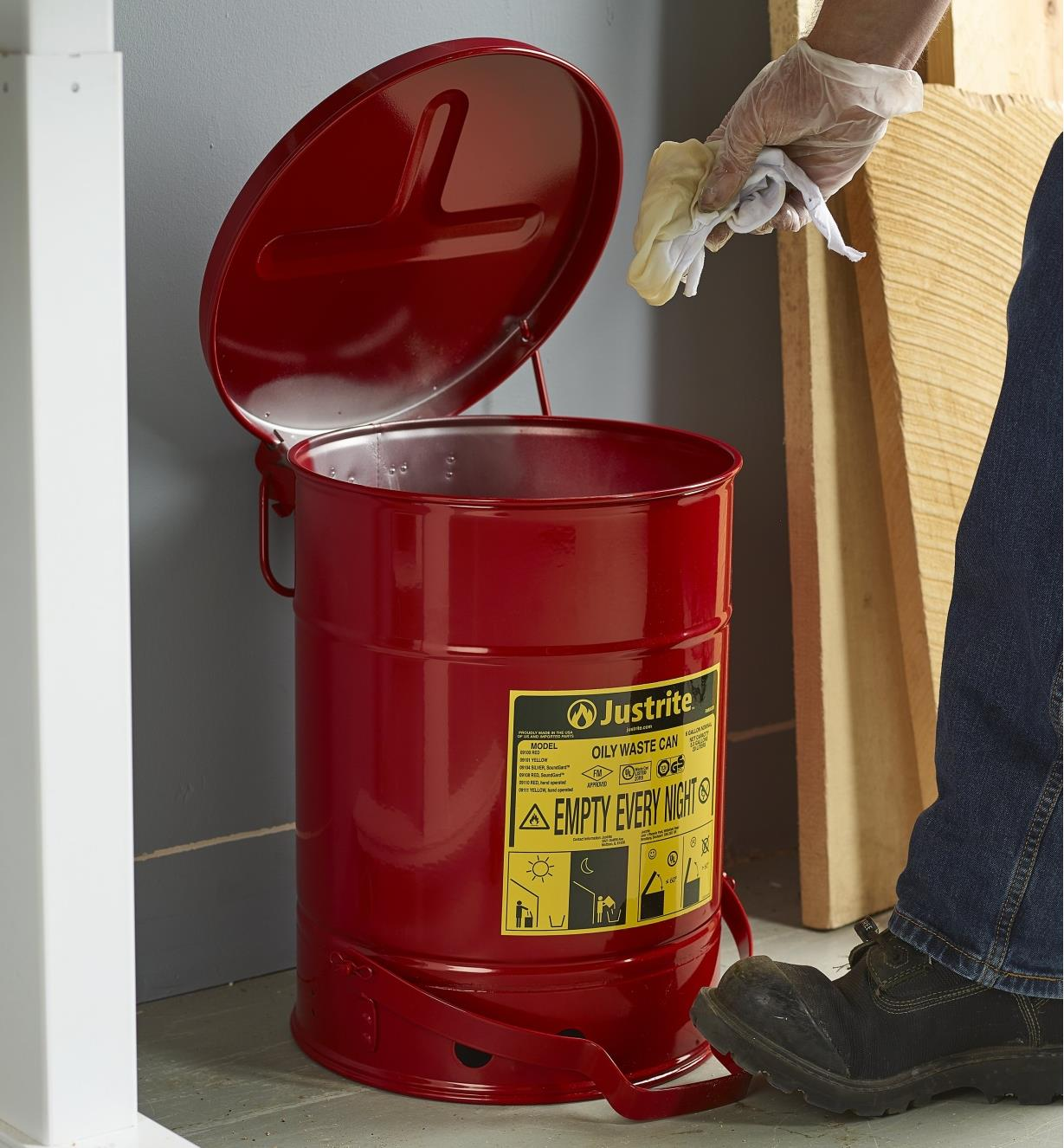 Discarding an oil-soaked rag in a flammable-waste can in a workshop