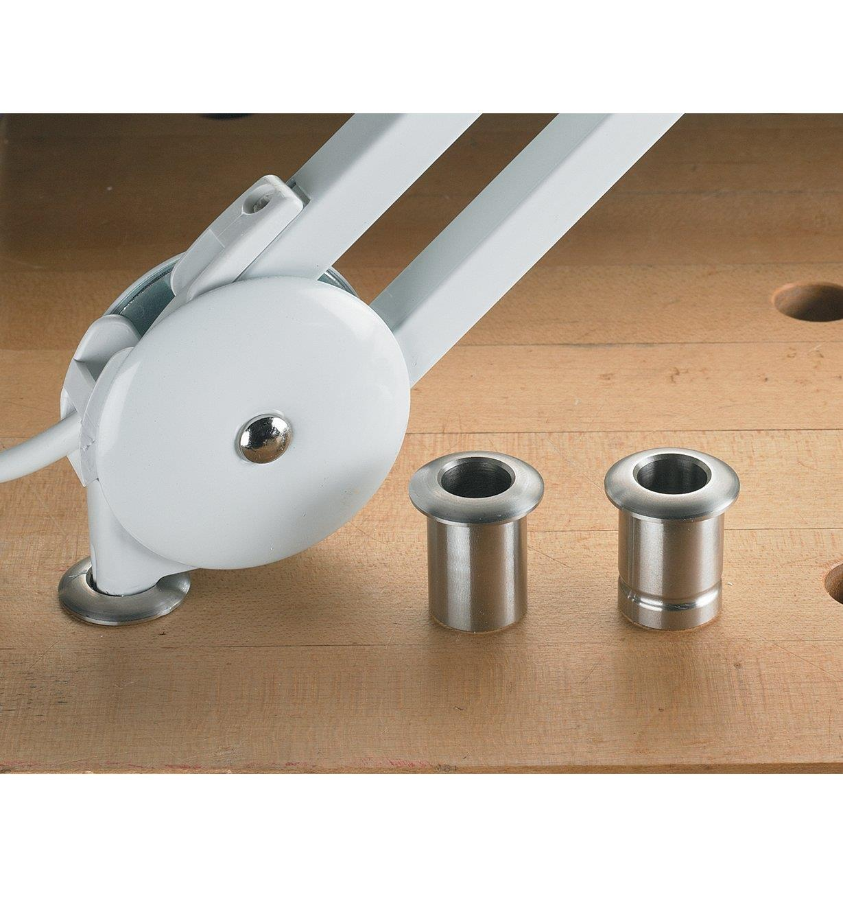 Both sizes of lamp bushing placed on a workbench next to a lamp that is inserted into another bushing in a dog hole