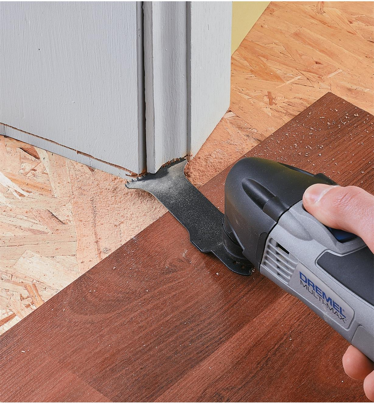 Multi-tool blade used to cut out a slot in wall trim for installing floorboards