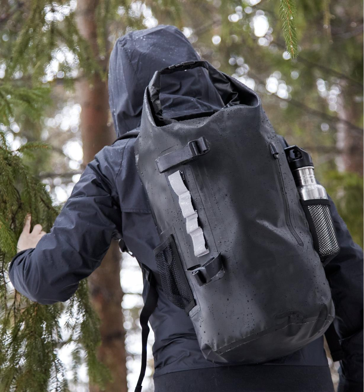 A rain-splashed hiker wears a waterproof dry bag backpack that has a drink bottle in the mesh side pocket