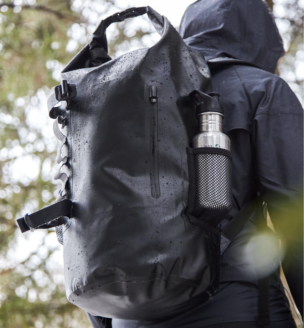 Side view of waterproof dry bag backpack showing a closed zippered pocket and a mesh pocket holding a drink bottle