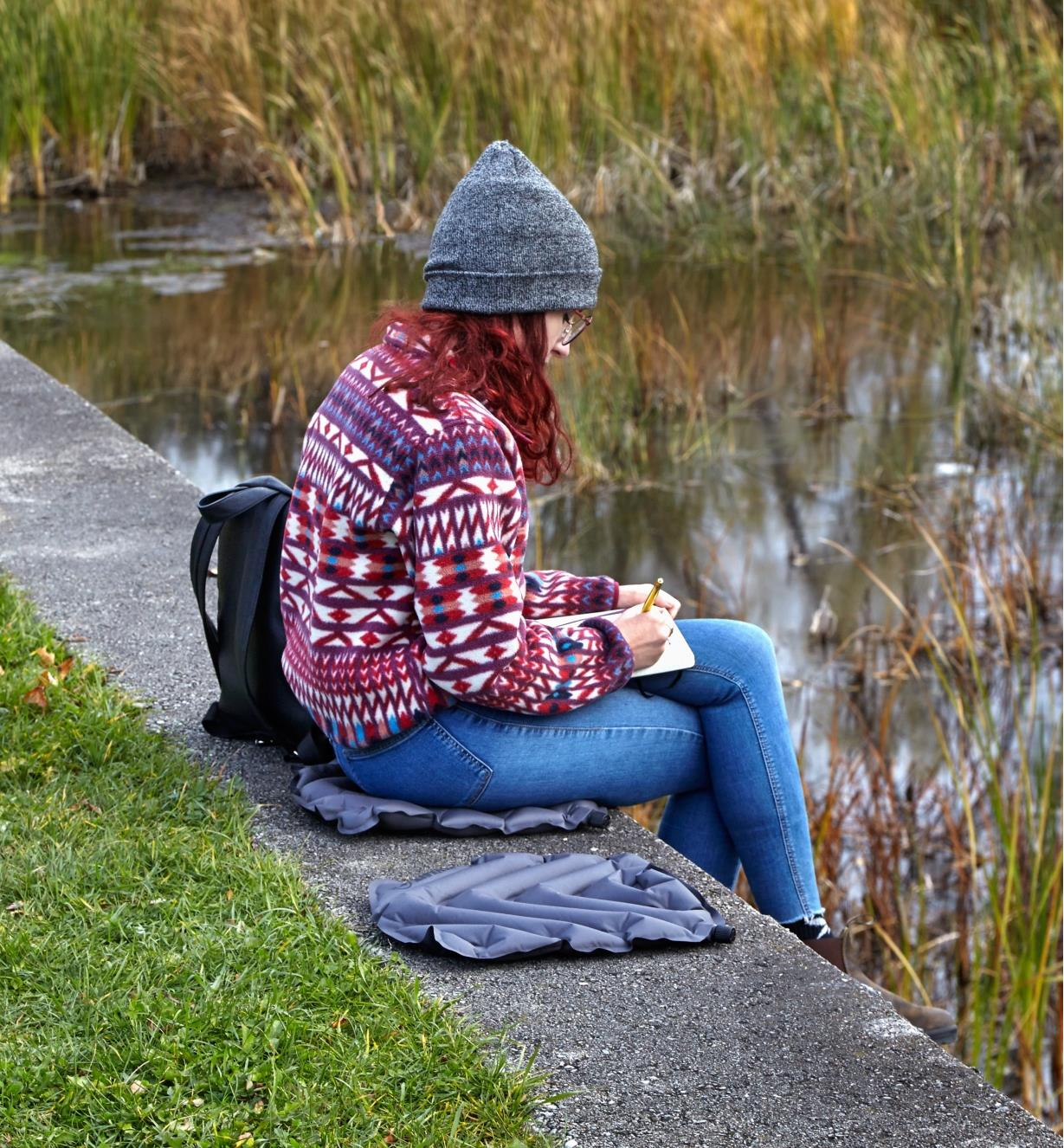 A woman sits on an inflatable seat cushion placed on a concrete ledge while writing notes outdoors