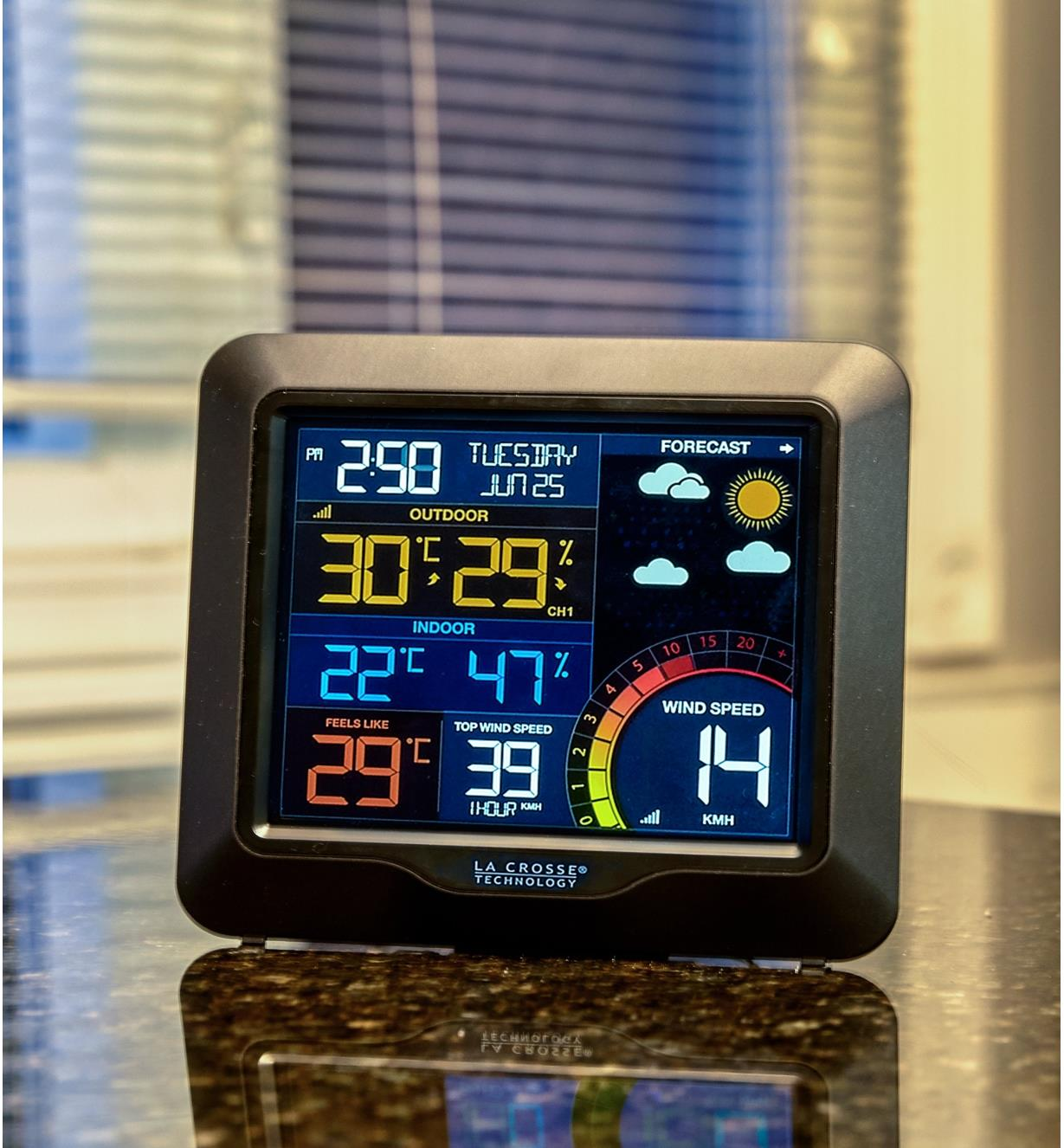 LCD screen of the wireless weather station displays date, time, forecast icons, temperature and humidity in celsius and wind speed in kilometres per hour