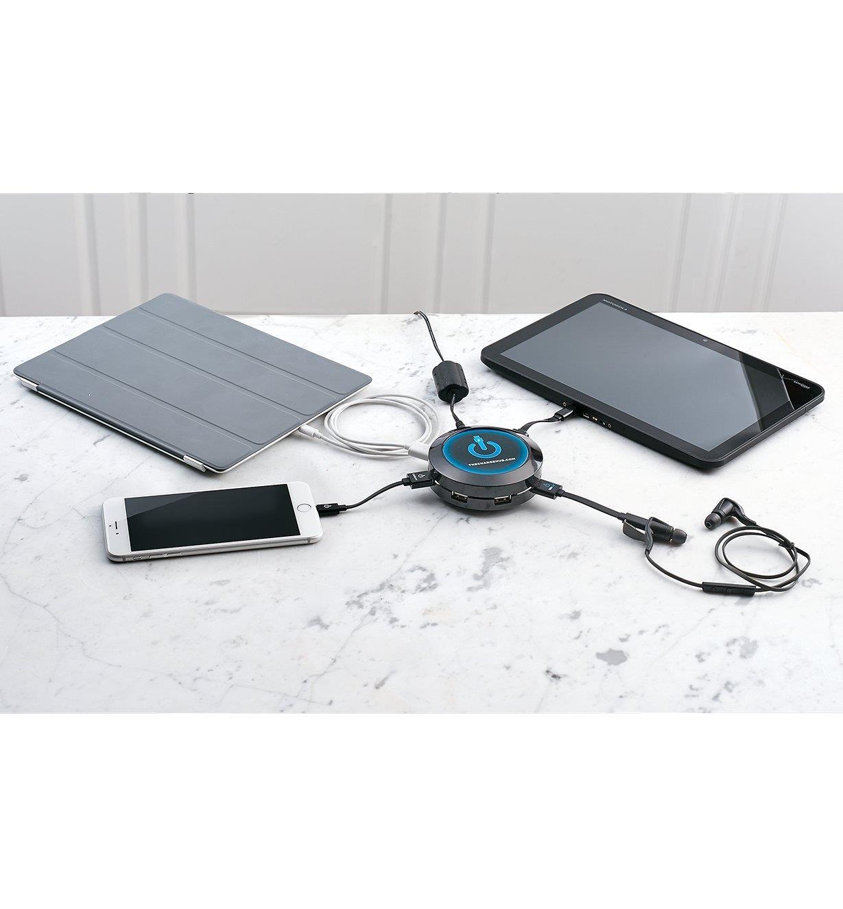 Ordinateur portable, tablette, écouteurs sans fil et téléphone cellulaire connectés à la station de recharge posée sur un comptoir en marbre